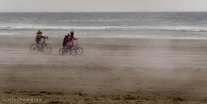 Bikes on the beach riding through the fog
